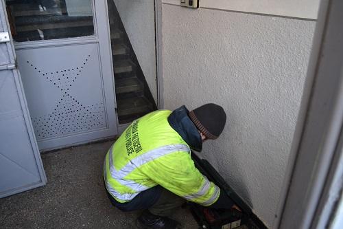 angajatul Primăriei Fălticeni scotând din trusă cele necesare spargerii unei uși de asociații de proprietari